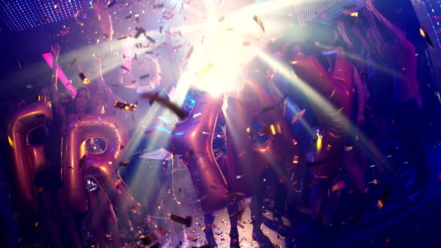 Group of friends dancing in a nightclub holding FRIYAY balloons video