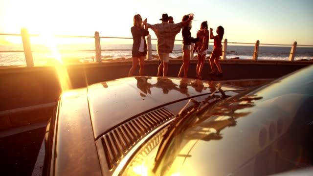 Gruppo di amici ballare in parte anteriore di mare - video