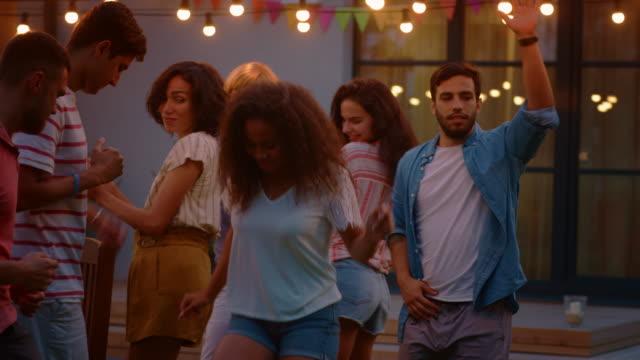 vídeos y material grabado en eventos de stock de grupo de amigos bailando juntos en la celebración de la fiesta de jardín. hermoso y guapo personas divirtiéndose en el patio de la casa en una noche de verano. en cámara lenta. - fiestas al aire libre