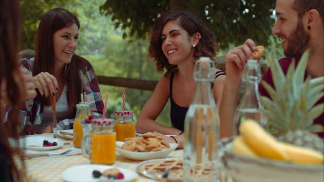 vídeos de stock e filmes b-roll de group of friends doing breakfast outdoors in a traditional countryside. shot in slow motion - sumo