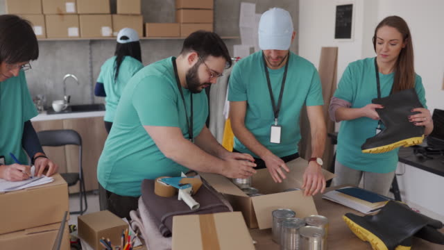 Group of friends doing charity work in charitable foundation Group of mixed race volunteers working in charitable foundation, packing donation boxes giving tuesday stock videos & royalty-free footage