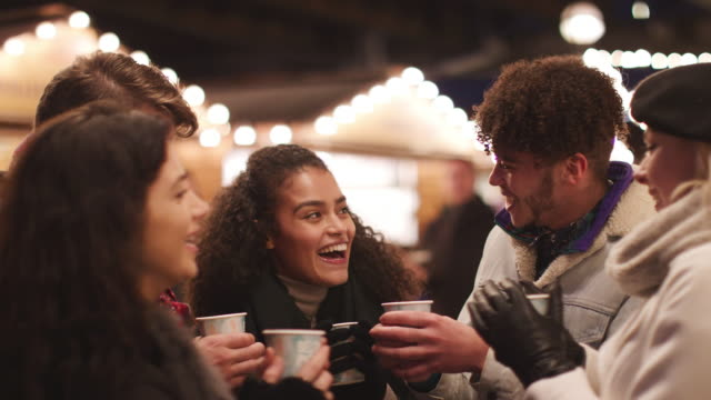 Group Of Friends Drinking Mulled Wine At Christmas Market video