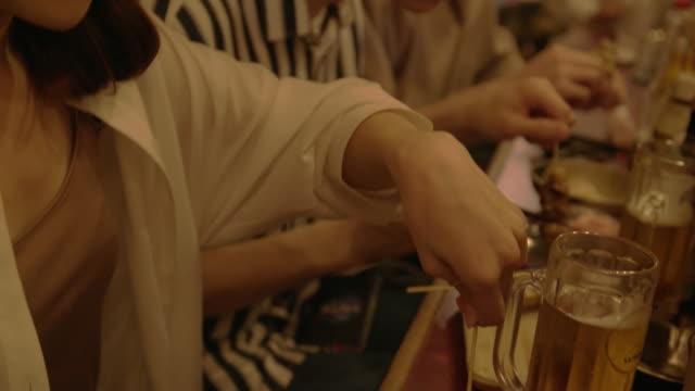 Grupo de amigos comer y beber en el Izakaya. - vídeo