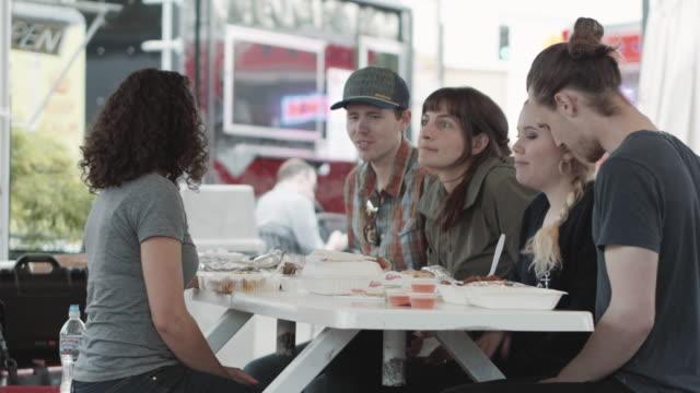 stockvideo's en b-roll-footage met groep vrienden eten bij voedsel-trucks - foodtruck