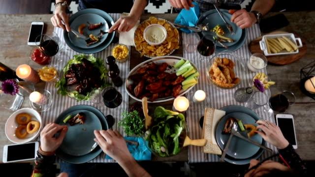 stockvideo's en b-roll-footage met groep vrienden eten kippenvleugeltjes, bovenaanzicht - breakfast table