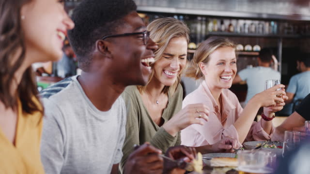 Group of friends eating meal and talking in busy restaurant - shot in slow motion