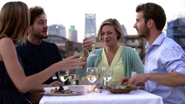 group of friends eating meal on rooftop terrace - vitt vin glas bildbanksvideor och videomaterial från bakom kulisserna
