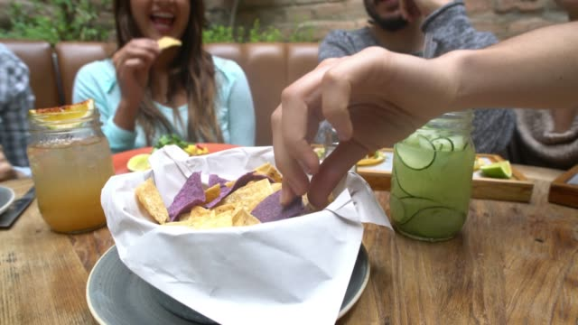 Group of friends eating Nachos at a restaurant video