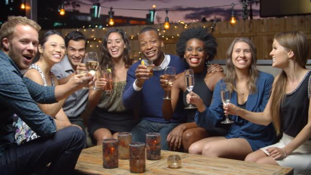 gruppo di amici, godetevi la serata al bar sul tetto, rallentatore - happy hour video stock e b–roll