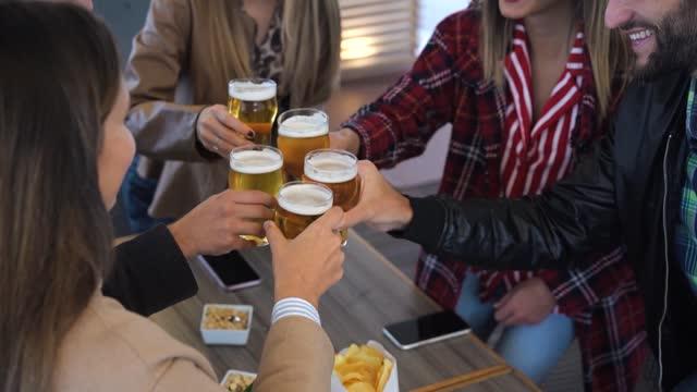 gruppo di amici che si godono una birra nel pub vintage del birrificio - giovani mani che tifano al ristorante del bar - amicizia, festa, vita notturna e concetto di gioventù - antipasto video stock e b–roll