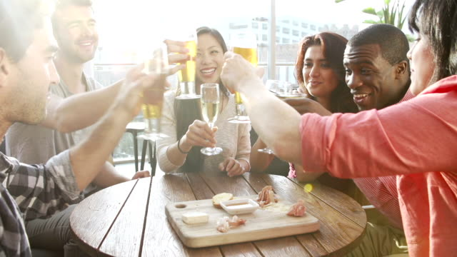 Group Of Friends Enjoying Drink In Bar Group of friends make a toast as they enjoy drinks and snacks in rooftop bar in slow motion.Shot on Sony FS700 in PAL format at a frame rate of 50fps bar counter stock videos & royalty-free footage