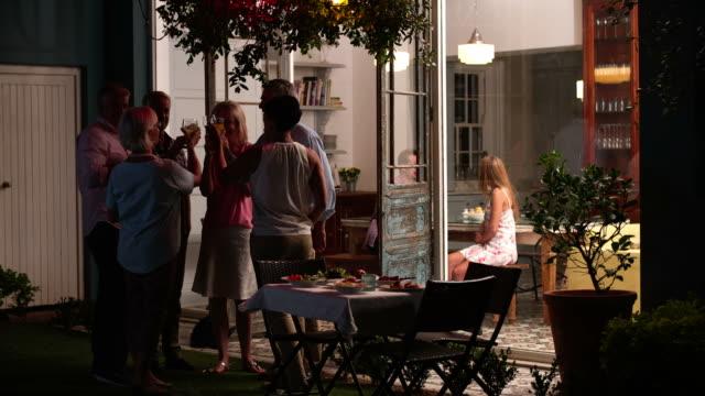 Grupo de amigos disfrutando de bebidas por la noche de fiesta al aire libre - vídeo