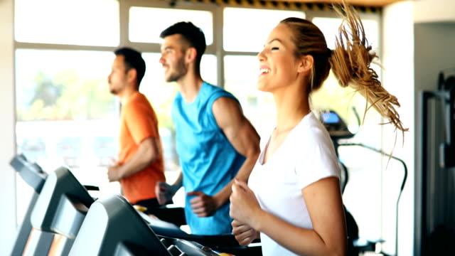 group of friends exercising on treadmill machine - sala gimnastyczna miejsce rekreacji filmów i materiałów b-roll