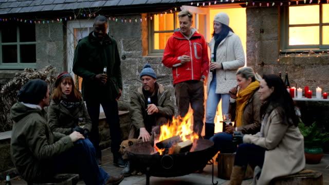 Grupo de amigos se reunieron alrededor de un fogón - vídeo