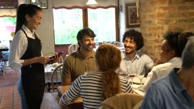 group of friends giving order to waitress at restaurant - kelner filmów i materiałów b-roll
