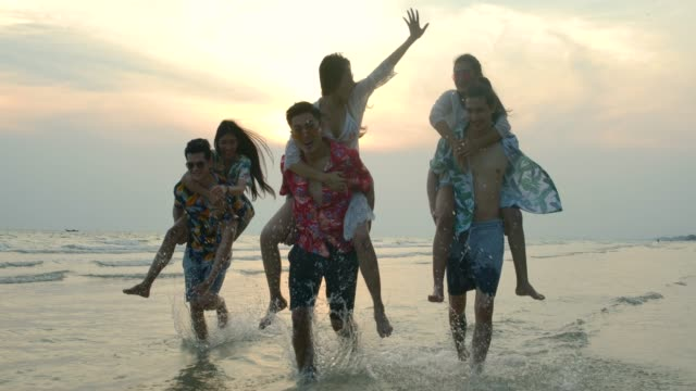 Group of friends giving piggyback rides to girls at the beach in slow motion. Summer, Travel and Beauty concept.