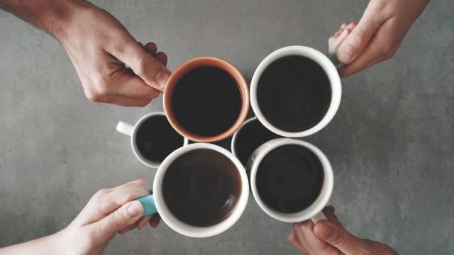 Group of friends hands holding cup of coffee Group of friends hands holding cup of coffee cheering stock videos & royalty-free footage