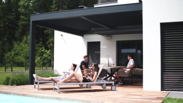 Group of friends hanging out by the pool