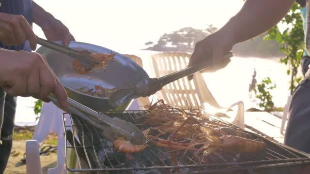 gruppe von freunden mit grill schweinefleisch garnelen und meeresfrüchte-party-event am strand - fische und meeresfrüchte stock-videos und b-roll-filmmaterial