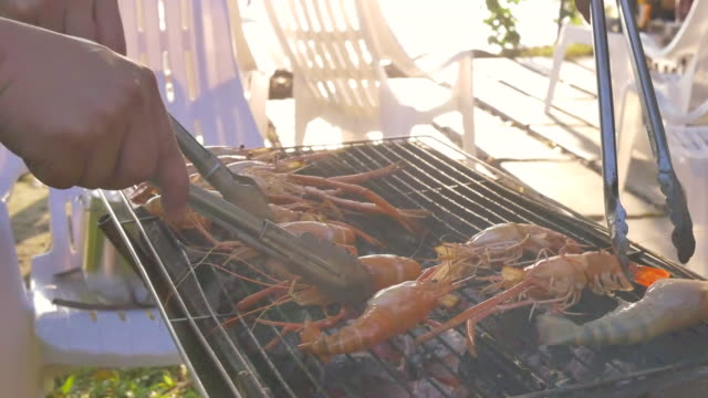 Group of friends having barbecue pork shrimp and seafood party event on beach Group of friends having barbecue party event on summer beach shrimp seafood stock videos & royalty-free footage