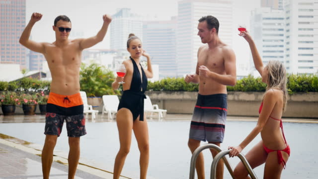 Group of friends having fun dancing and drinking beer at swimming pool outdoors, people, vacation and summer concept Group of friends having fun dancing and drinking beer at swimming pool outdoors, people, vacation and summer concept pool party stock videos & royalty-free footage