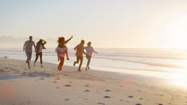 Group Of Friends Having Fun Running Along Winter Beach Together Group of friends running and giving piggybacks to each other on winter beach with sun flaring into lens medium group of people stock videos & royalty-free footage