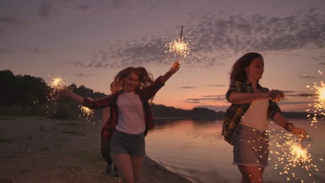 bir grup arkadaş sahilde kıvılcımlarla koşarak eğleniyor. - mum aydınlatma ürünleri stok videoları ve detay görüntü çekimi