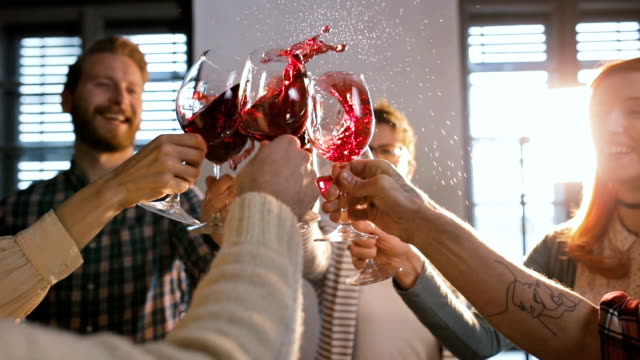 group of friends having fun while toasting with wine and splashing it. - office party stock videos and b-roll footage