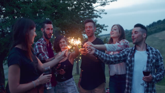group of friends having fun with sparklers. shot in slow motion group of friends having fun with sparklers. shot in slow motion aperitif stock videos & royalty-free footage