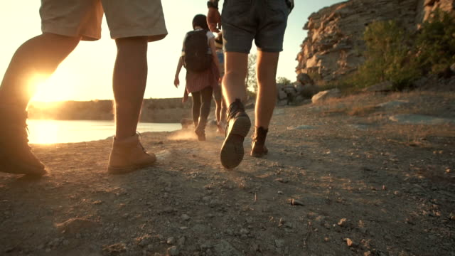 Group of friends hiking on rocky coastline Low angle view of feet of tourists walking at sunset on a rock near the lake. Slow motion group of people stock videos & royalty-free footage