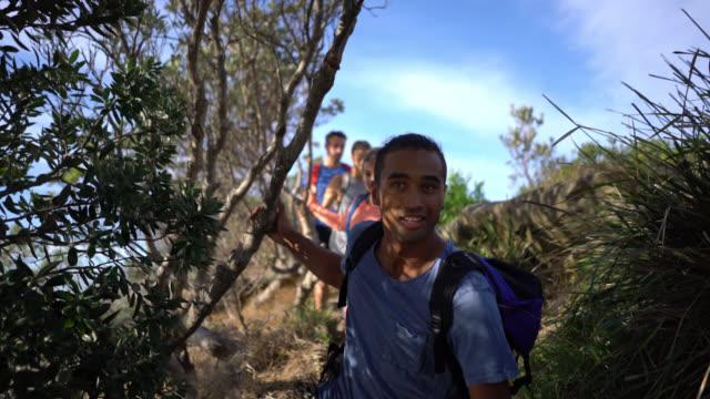 group of friends hiking outdoors walking in a line - ekoturystyka filmów i materiałów b-roll