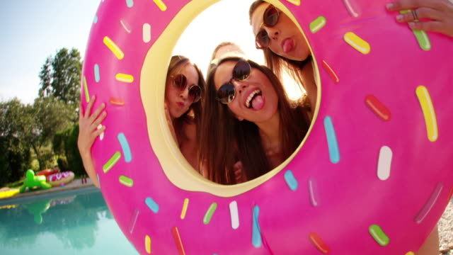 Group of friends holding a pool inflatable like a frame Laughing group of girl friends holding a pink donut novelty pool inflatable up in front of them like a photo frame outdoors in the sun pool party stock videos & royalty-free footage