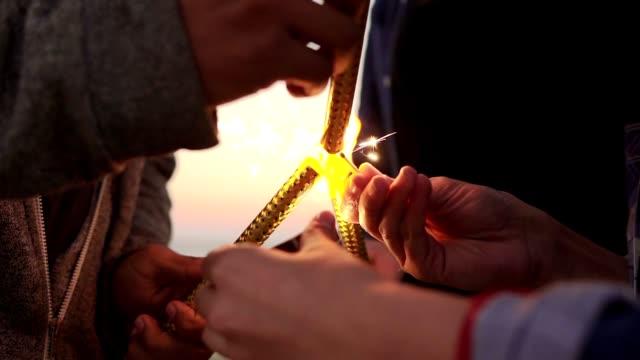 友人のグループ保持して輝くキャンドルと日没時にビーチにそれらを軽く - ガールパワー点の映像素材/bロール