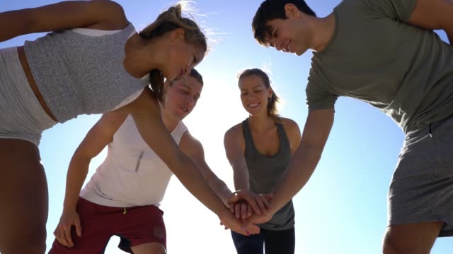 stockvideo's en b-roll-footage met groep vrienden huddling allen met handen in op het strand - huddle