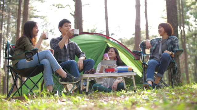 Group of friends in outdoor camping at pine campsite area enjoying in front of a tent