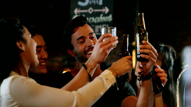 Group of friends interacting while toasting beer bottles video