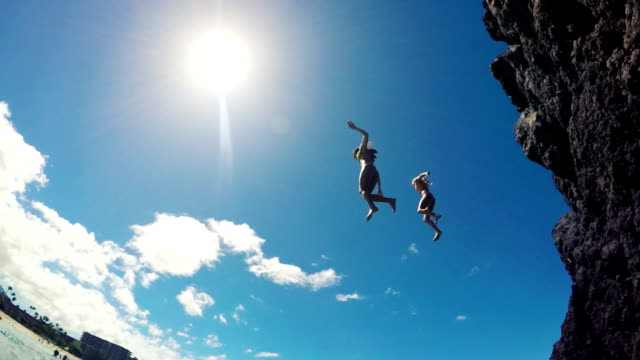Group of friends jumping from cliff into the ocean in Hawaii. Water Shot Underwater Angle POV.