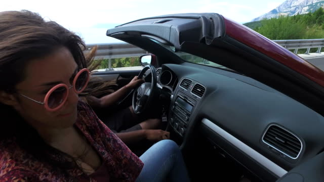 vidéos et rushes de groupe d'amis, écouter de la musique en cabriolet rouge - homme faire coucou voiture
