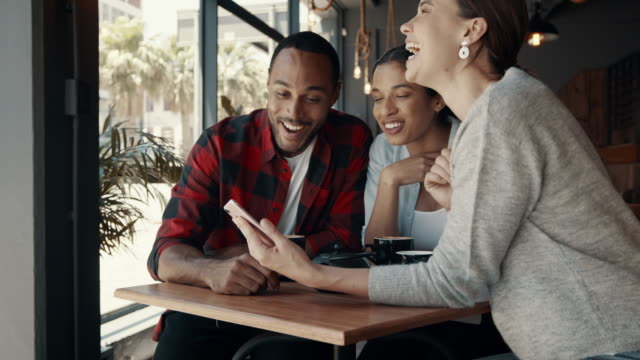 Group of friends looking at mobile phone and laughing at a coffee shop