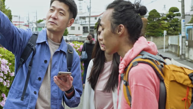 Group of friends looking for guidance with the smartphone help visiting Tokyo Group of friends looking for guidance with the smartphone help visiting Tokyo, They are in the street pointing where it could be in relation where they are. guidance stock videos & royalty-free footage