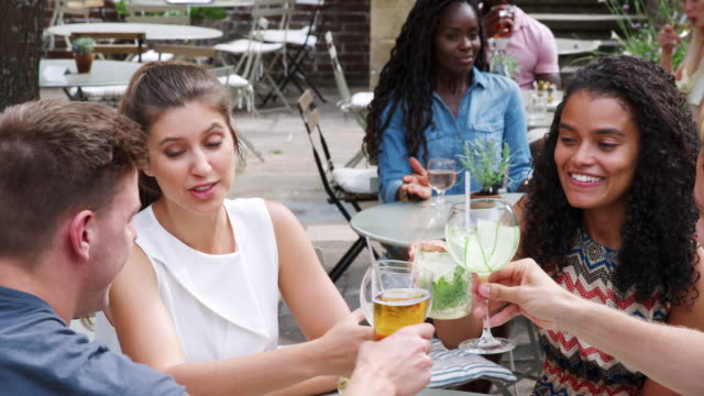 group of friends meeting for drinks at outdoor tables in restaurant - terrazza video stock e b–roll