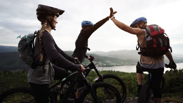 Group of friends mountainbike riders: MTB biking outdoor up mountain of Norway