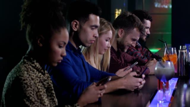 Group of friends networking on phones in nightclub