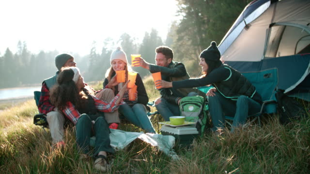Group of friends on a camping trip sitting outside a tent video