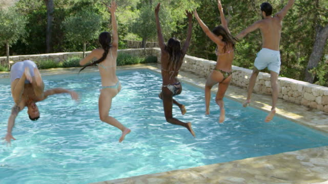 Group Of Friends On Vacation Jumping Into Outdoor Pool video