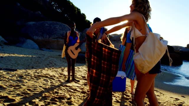 stockvideo's en b-roll-footage met groep vrienden picknickkleed plaatsen op het strand 4k - rocks sea