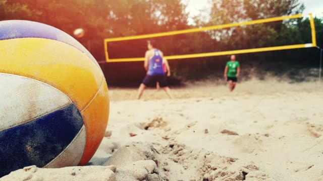 group of friends playing beach volleyball closeup of ball in sand group of friends playing beach volleyball closeup of ball in sand volleyball ball stock videos & royalty-free footage