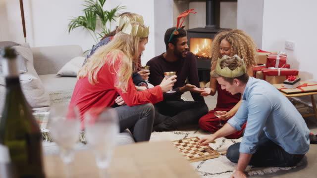 gruppo di amici che giocano a giochi da tavolo dopo aver gustando la cena di natale a casa - pranzo di natale video stock e b–roll