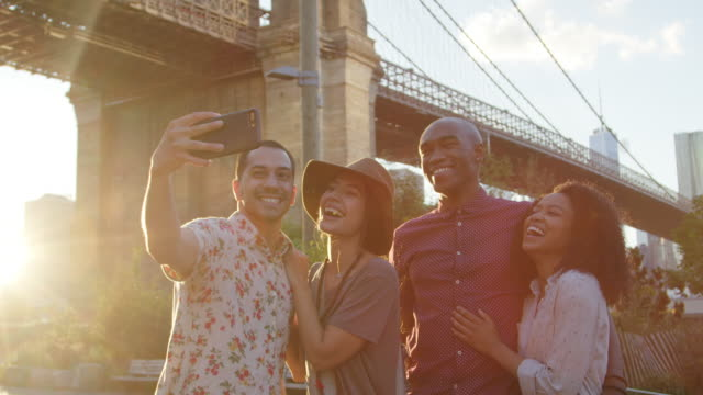 grupp av vänner som poserar för selfie framför brooklyn bridge - rörlig aktivitet bildbanksvideor och videomaterial från bakom kulisserna