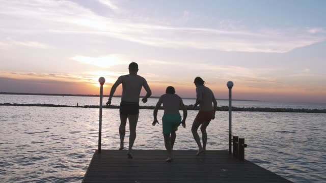 grupp vänner kör och hoppa från havet piren i vattnet under vackra solnedgången, slowmotion - kille hoppar bildbanksvideor och videomaterial från bakom kulisserna